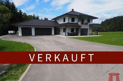 Modernes Einfamilienhaus mit großer Garage und Bachlauf